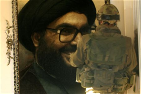 IDF soldier looks at portrait of Nasrallah
