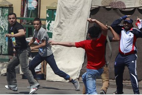 Supporter of Morsi (in red) clashes with anti