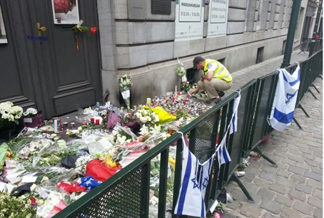 Man lays flowers at memorial outside Brussels