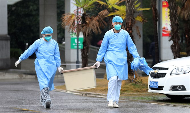 Medical staff carry a box as they walk at the Jinyintan hospital